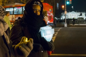 Denise Anderson holds a luminary in her arms as she takes part in a vigil on 16th Street near the White House in Washington. Thousands of demonstrators were expected in Washington and New York to protest the killings of unarmed black men by US police and to urge Congress to protect citizens. – Reuters pic, December 13, 2014.