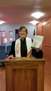 Sarah Howe Miller holds her copy of the book - in the pulpit!