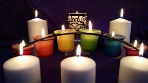 A dozen candles of various shapes, sizes, amd colors
