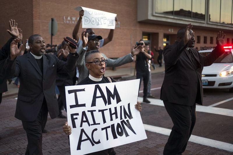 Clergymen shout as they march to the County Prosecutor McCulloch's office to protest the shooting death of unarmed black teen Michael Brown in Clayton, Missouri