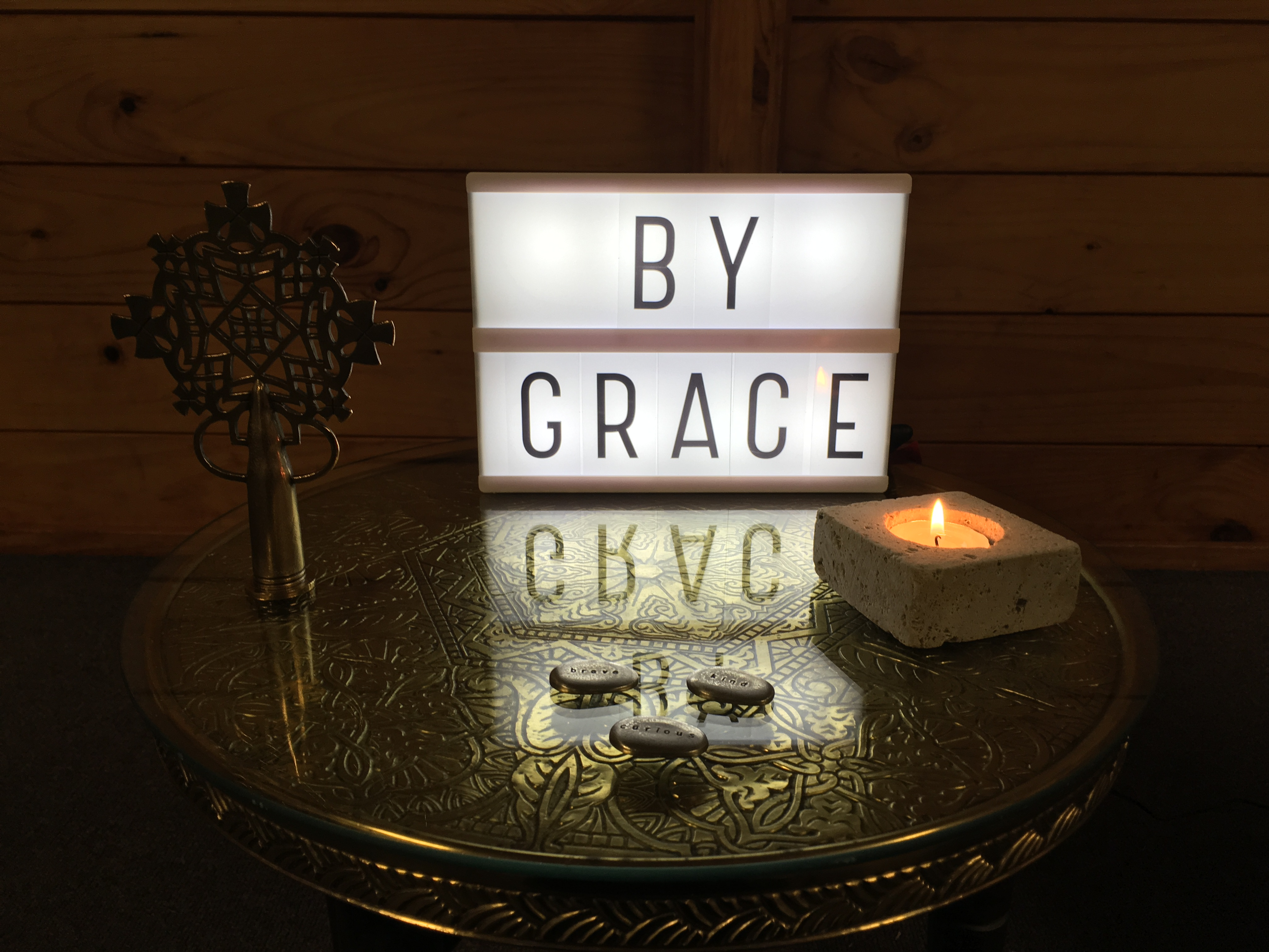 "A light box reads ""By Grace"", There is a cross on the table next to it, a candle lit in front of it and three pebbles. The pebbles have a word on each of them: brave, curious, kind."