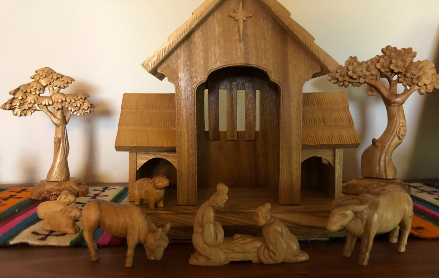Wooden nativity set showing Mary and Joseph with a baby, accompanied by an oxen, donkey and sheep.