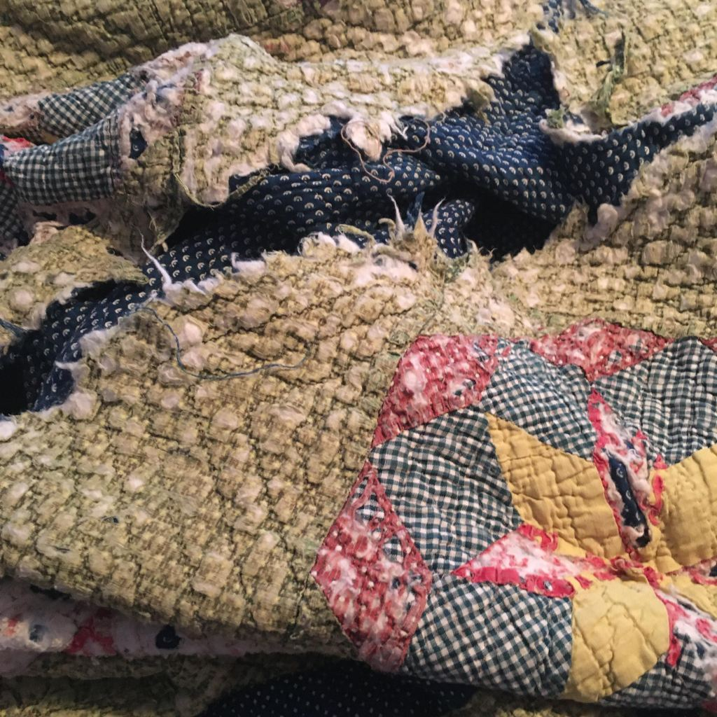 Photo of a torn, frayed antique quilt in light green, navy blue, red and yellow.