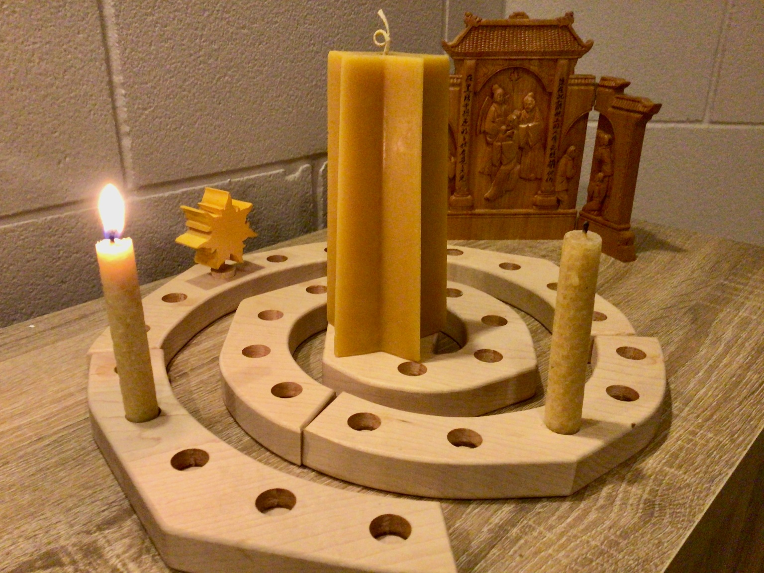 Lit candle in a wooden Advent spiral, with wooden sun peg several slots ahead to mark the passing of the week.