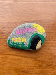 small stone painted with 'alleluia' and an empty tomb, flowers, and sun