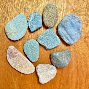 smooth stones of varying shapes and colours against a wooden table background