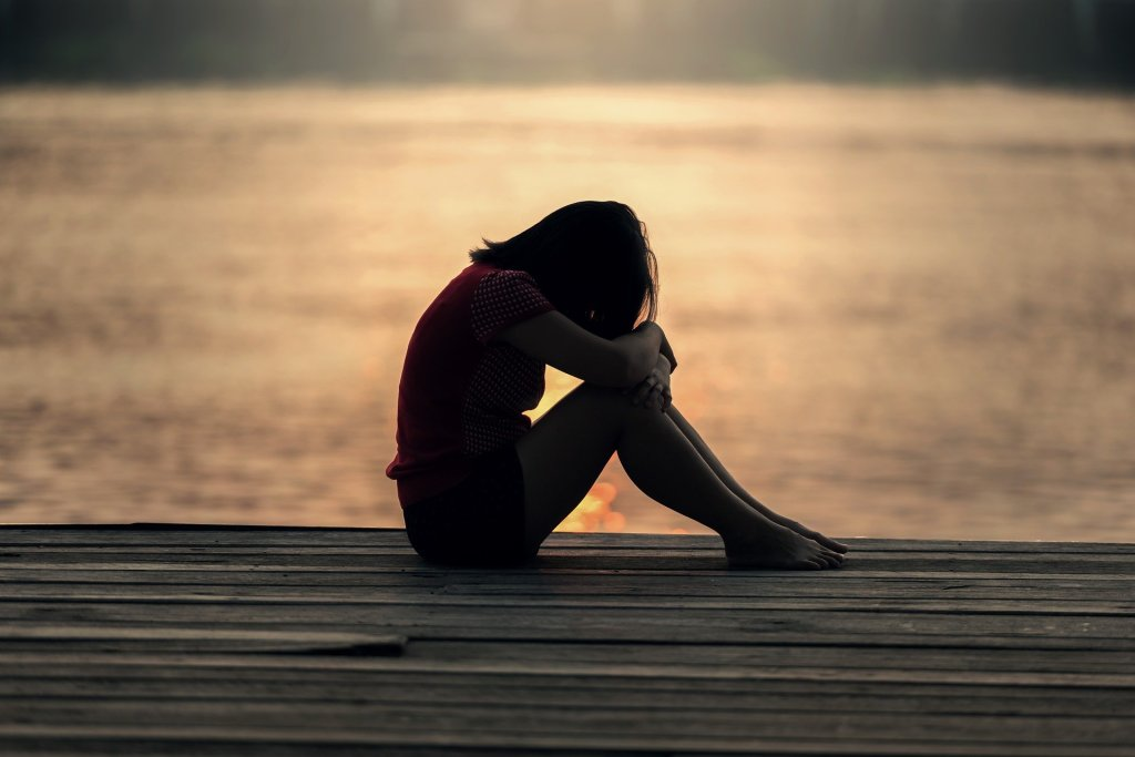 Image shows a girl with her head and knees bent as she sits. The sun glows behind her.