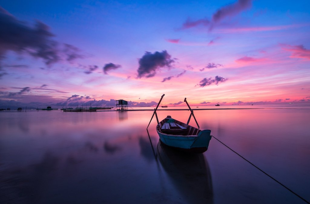 A boat floats on a lake at sunrise